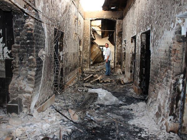 On Oct. 16, 2015, an employee of Doctors Without Borders stands inside the charred remains of the organization's Kunduz hospital following a U.S. airstrike.