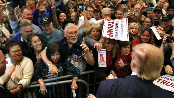 Donald Trump stops as supporters reach out for him to sign autographs during an October rally in Nevada.