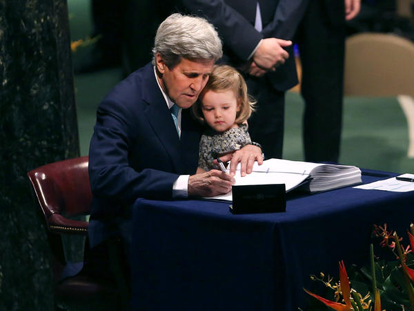 Secretary of State John Kerry holds his 2-year-old granddaughter, Isabel Dobbs-Higginson, as he signs a far-reaching climate accord at the United Nations, in a ceremony timed to coincide with Earth Day on Friday.