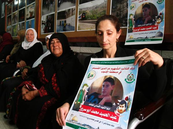 The mother (right) of Abdel Hamid Abu Srour (portrait) mourns with family members as she receives condolences at the Al-Ruwad Center in the Aida Refugee Camp near Bethlehem on Friday.