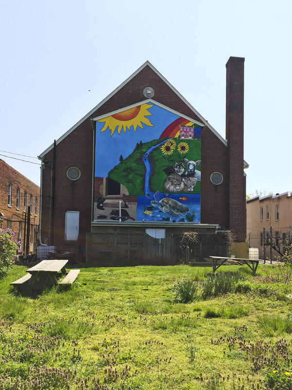 A large mural covers the back side of the Amazing Grace Lutheran Church in East Baltimore. It backs onto a park created by the Charm City Land Trust in an area where abandoned homes once stood.