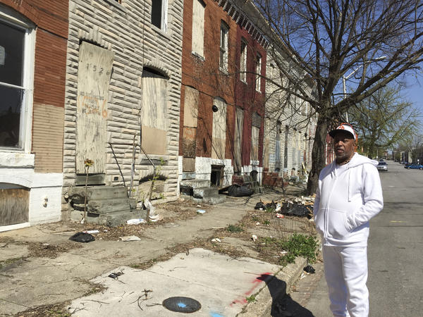Marvin Cheatham, president of the Matthew Henson Neighborhood Association, stands in front of a row of abandoned homes in West Baltimore. He would like to see them torn down and replaced by a food market, a senior center and a health clinic — all of which the neighborhood currently lacks.