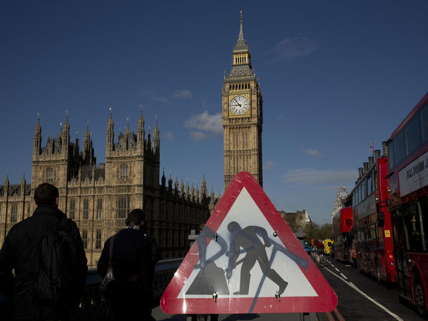 Big Ben resides in the Elizabeth Tower of the Houses of Parliament, seen in the distance behind a construction sign on Westminster Bridge.