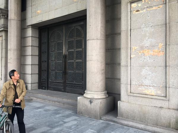 A pedestrian walks past the building on the Bund, Shanghai's colonial waterfront, that until recently held Zhongjin Capital Management. Police raided the firm earlier this month and arrested more than 20 company officials. The company signs have been torn down.