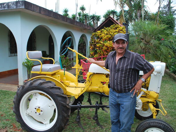 Danilo Garcia outside his home in San Raymundo, Guatemala, with a tractor he bought in Riverhead, N.Y.