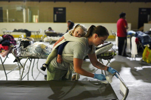 Marlee Hildebrandt and her 2-year-old daughter, Oakley, clean cots at a makeshift evacuee center in Lac la Biche, Alberta, on Thursday, after fleeing forest fires.