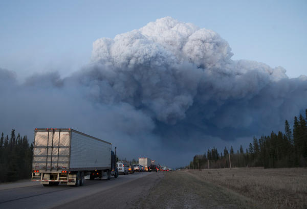 Drivers wait outside Fort McMurray for clearance to take firefighting supplies into town on Thursday.