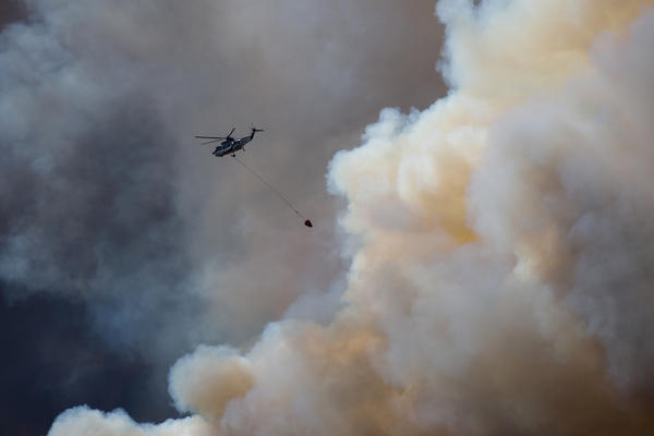 A helicopter flies into thick smoke while battling a major forest fire outside of Fort McMurray on Wednesday.