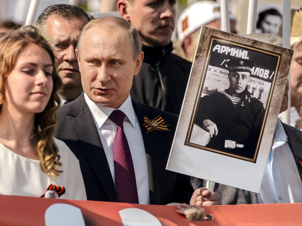 Russian President Vladimir Putin holds a portrait of his father, who fought in World War II, during Monday's Moscow parade marking Victory Day in Russia.