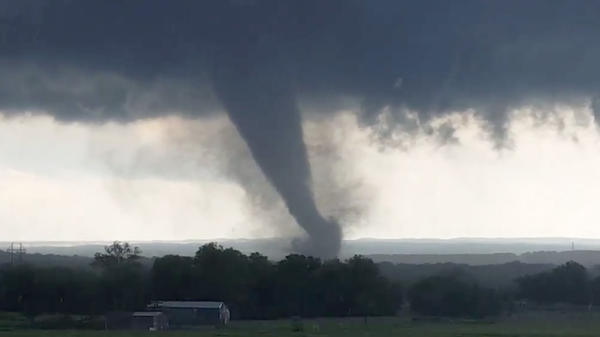 """This image, made from a video taken through a car window, shows a tornado near Wynnewood, Okla., on Monday. A broad tornado capable of leaving """"catastrophic"""" damage in its wake churned across the Oklahoma landscape Monday, prompting forecasters to declare a tornado emergency for two communities directly in its path."""