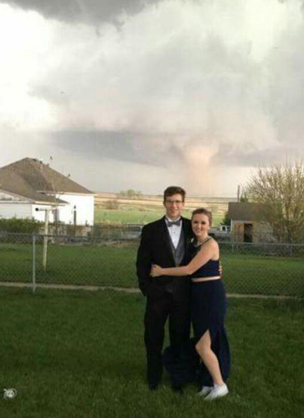 Charlie Bator (left) and Ali Jolie Marintzer pose for a prom photograph — with tornado — near Wray, Colo., on Saturday.
