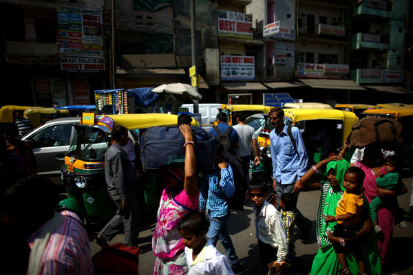 Crowds of pedestrians do battle with the traffic on the streets of New Delhi near the central train station.