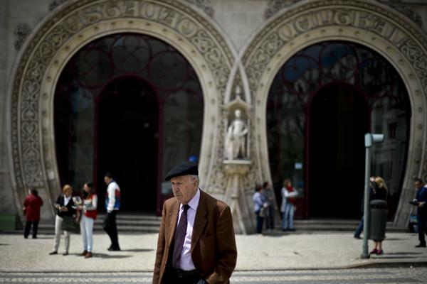 A man passes in front of Rossio train station in 2014 (when King Sebastian still stood watch).