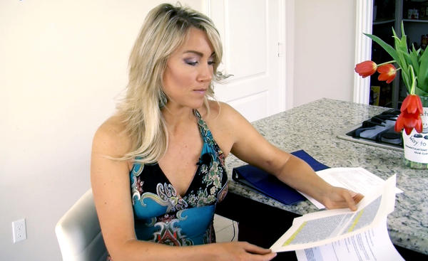 Navy veteran Amanda Wirtz looks through her correspondence with the Veterans Choice program. After the VA couldn't get her an appointment with a specialist, it sent her to the Choice program. But she still was unable to get an appointment for several months.