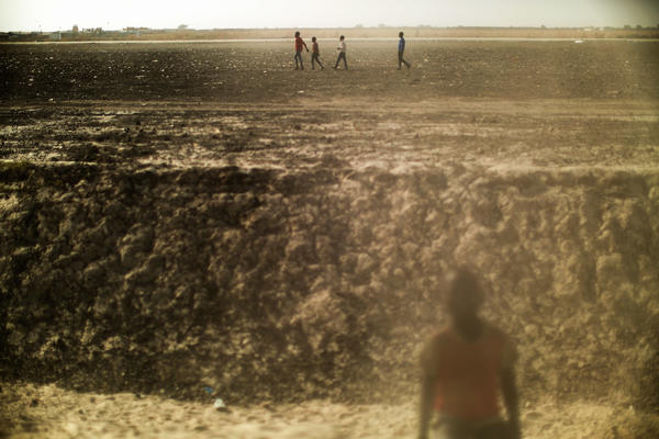 Residents walk across a dusty plain inside the U.N. Protection of Civilians camp near Bentiu, South Sudan.