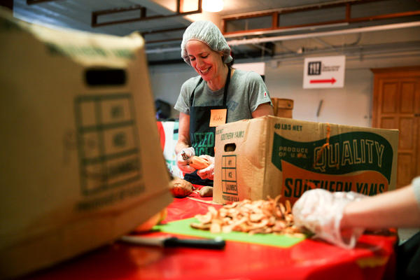 A volunteer peels sweet potatoes.