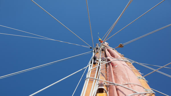 The mast must come down in the next part of the journey to get past the bridges on the Potomac River on the way to the Washington, D.C., stop. The lei at the very top is color coded; traditionally each captain had his own color so the boats could recognize who was on it from afar.