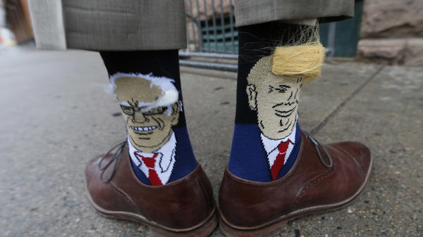 Colorado Gov. John Hickenlooper shows off his socks — one with Democratic presidential candidate Bernie Sanders and the other with Republican candidate Donald Trump.