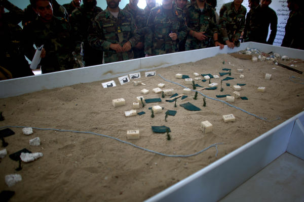 Afghan commandos stand around a sandbox table, studying a model of the village they are about to sweep from Taliban fighters. Styrofoam buildings and green toothpick trees are carefully placed to create a realistic view of the village.