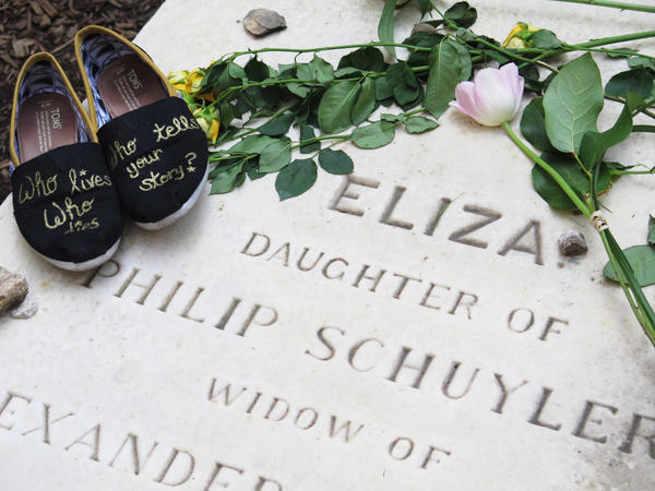 Visitor Stacy Kmentt photographed her shoes, which she decorated with a lyric from the musical, on top of Eliza Hamilton's gravestone in New York City.