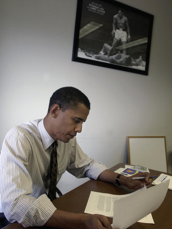 Barack Obama in 2004, then a candidate for U.S. Senate, reading through a copy of his keynote speech to the Democratic National Convention below a photo of Muhammad Ali at his campaign office in Chicago, Ill.