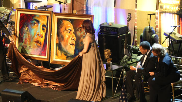 Muhammad Ali, sitting with wife Lonnie Ali, is presented with two paintings at the Bluegrass Ball, the day before Barack Obama's inauguration in 2009.