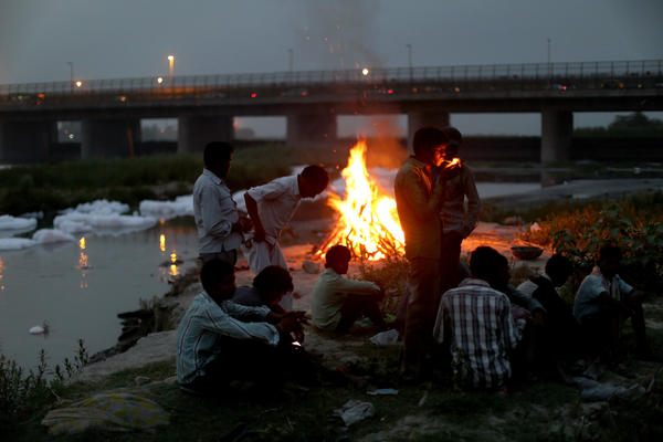 """Men watch the fires of a cremation along the banks of the Yamuna River against the backdrop of the Wazirabad Barrage and floating industrial waste. <em>From the story """"<a href=""""http://www.npr.org/2016/05/11/477415686/can-indias-sacred-but-dead-yamuna-river-be-saved"""" target=""""_blank"""">Can India's Sacred But 'Dead' Yamuna River Be Saved</a>,"""" 2016.</em>"""