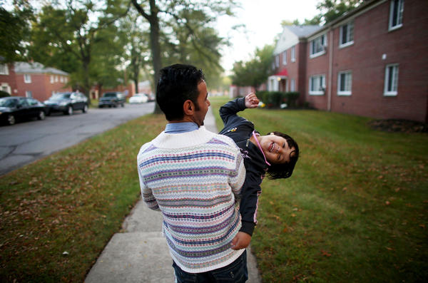 """Omar Al-Awad holds his daughter as they walk home in Toledo, Ohio, where they were recently resettled after fleeing Syria and living in a Jordanian refugee camp. <em>From the story """"<a href=""""http://www.npr.org/2015/10/20/450221327/among-the-lucky-few-syrian-family-rebuilds-in-americas-heartland"""" target=""""_blank"""">Among The Lucky Few: Syrian Family Rebuilds In America's Heartland</a>,"""" 2015.</em>"""