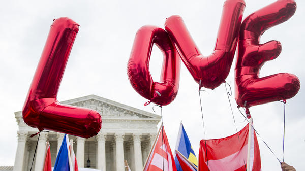 """Same-sex marriage supporters from the Human Rights Campaign fly """"LOVE"""" balloons Jun 26, 2015, in front of the U.S. Supreme Court as they await the court's decision in a same-sex marriage case. The justices' ruling legalized it nationwide."""