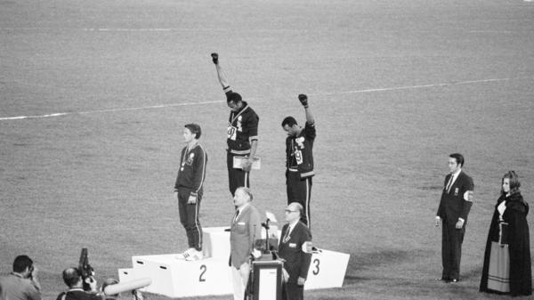 Tommie Smith and John Carlos, gold and bronze medalists in the 200-meter run at the 1968 Olympic Games, engage in a victory stand protest against unfair treatment of African-Americans in the United States. Australian Peter Norman is the silver medalist.