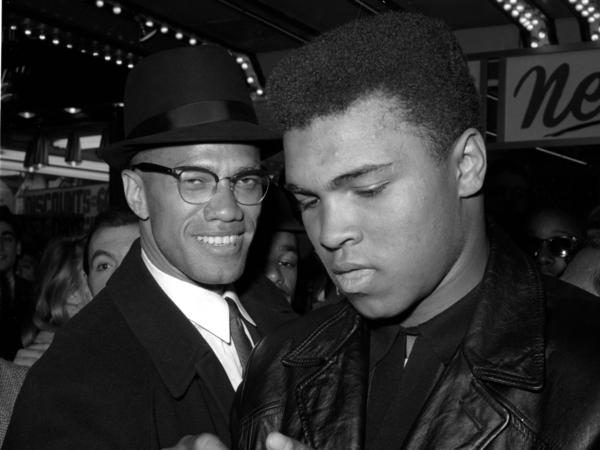 Muhammad Ali (right) is shown with Malcolm X, outside the Trans-Lux Newsreel Theater in New York City, after watching a screening of films on Ali's title fight with Sonny Liston on March 1, 1964.