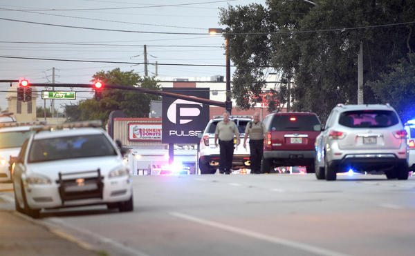 Police cars surround the Pulse Orlando nightclub, the scene of a fatal shooting, in Orlando, Fla.