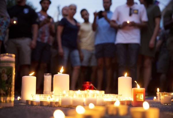 Mourners gather around candles lit during a vigil after the deadly shooting at the Pulse Orlando nightclub on Sunday.