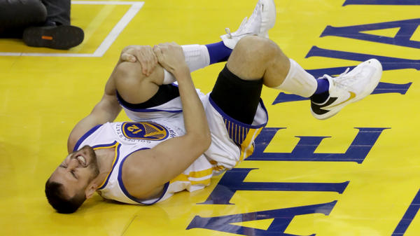 Andrew Bogut of the Golden State Warriors holds his knee in pain after sustaining an injury in the third quarter Monday night in Oakland.