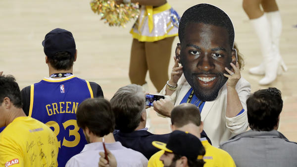 A fan holds up a cutout of Draymond Green's face Monday night. The Golden State Warriors player was suspended for Game 5 of the NBA Finals because of a flagrant foul he committed in the previous game.