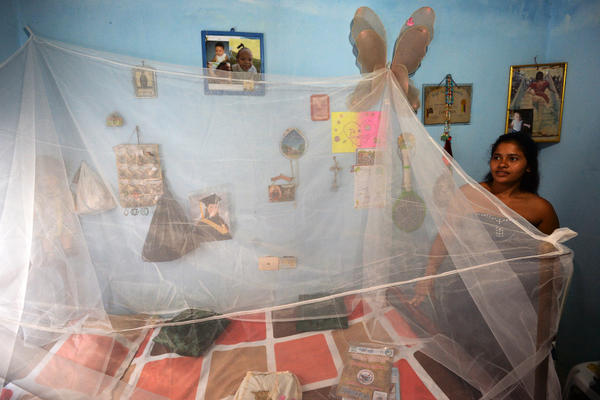 Eight months pregnant, Mara Torres stands next to a mosquito net placed over her bed in Cali, Colombia. Health officials in Cali have delivered mosquito nets to pregnant women to help protect them from the bites of mosquitoes that can transmit dengue, chikungunya or Zika.