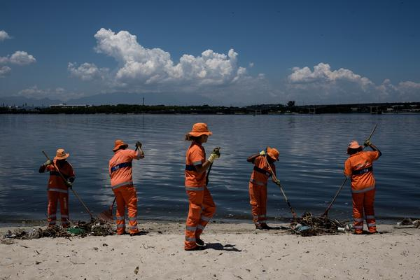 Cleaners in Rio de Janeiro collect debris from Guanabara Bay that washed up onto the beach last December. The bay, which will host sailing events at the Olympics in August, is heavily polluted.