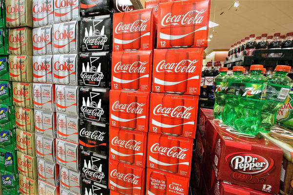 Sodas and energy drinks are stacked and line the shelves of a grocery store.