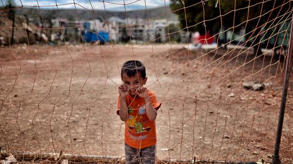 A boy looks on behind a net at the refugee camp of Schisto in Athens, Greece, on June 8.