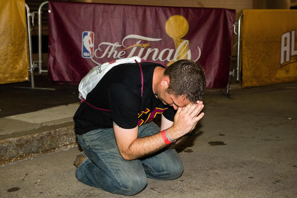 Cleveland fan Brian Wilson says a prayer during the final seconds of the game at the Cleveland Cavaliers NBA Finals Game Seven watch party at Quicken Loans Arena.