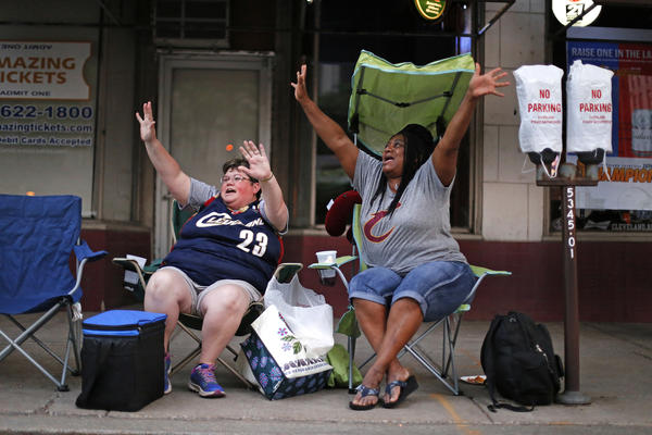 Misty Swegle (left) and Charlesetta Hawkins wave at passing motorists during rush hour on Tuesday in downtown Cleveland from their spot along the parade route for the city's celebration of the Cavaliers.