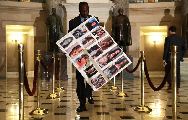 Charles Bolden, staff assistant of Rep. Robin Kelly, D-Ill., holds a poster with pictures of gun violence victims from Chicago as he walks toward the House Chamber on Wednesday in Washington, D.C.