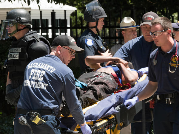 Paramedics rush a stabbing victim away on a gurney on Sunday, after clashes outside the California Capitol between white nationalist demonstrators and counterprotesters.