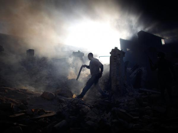 "A man carrying a shotgun walks through a collapsed burning building while trying to keep looters at bay on the streets outside Port-au-Prince, in January 2010. <a href=""http://www.npr.org/series/480930677/david-gilkeys-work/archive?date=1-31-2010"">Read the stories from Haiti.</a>"