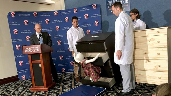 Elliot Kaye (left), chairman of the Consumer Product Safety Commission, and CPSC employees watch as an IKEA Malm model chest of drawers falls on a 28-pound dummy during a demonstration Tuesday at the National Press Club in Washington, D.C.