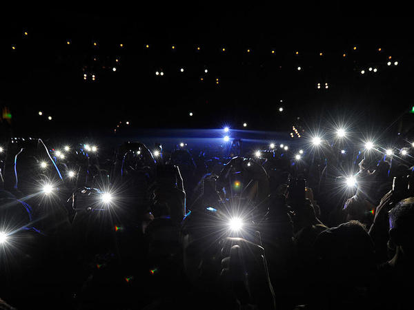 Fans hold up their phones at a Childish Gambino performance in 2014.
