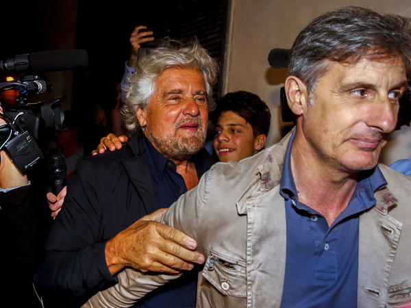 Beppe Grillo (left) arrives at a party in Rome on June 27 after his anti-establishment 5 Star Movement triumphed in Italian mayoral runoff elections in 19 cities.