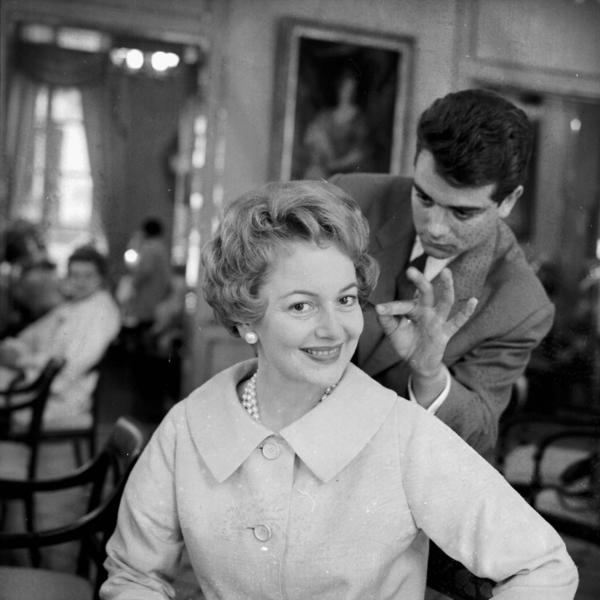 De Havilland smiles as she has her hair and makeup done in 1958.