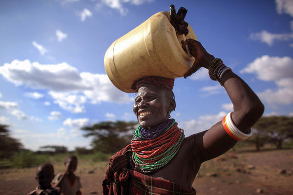 A woman from the remote Turkana tribe in Northern Kenya carries water from a well.