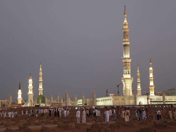 In this July 5, 2013, file photo, worshippers visit the cemetery outside the Prophet's Mosque in Medina, one of Islam's holiest sites. Medina was among the places attacked in Saudi Arabia on Monday.
